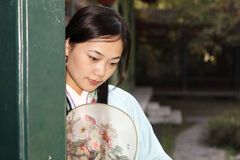 Retro beauty in China. A beautiful girl in Chinese ancient dress is in the royal garden Royalty Free Stock Photos