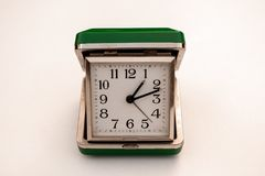 Retro rectangular bedside travel clock. Small dated green travel clock isolated on a white background royalty free stock image
