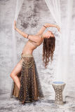 Retro belly dancer in backbend between drapes. A beautiful young belly dancer performs a backbend on a retro set with silk drapes Royalty Free Stock Photos