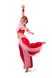 Retro belly dancer making an arabesque. A woman dressed in a retro belly dance costume (I dream of Jeannie style) makes an arabesque turn Royalty Free Stock Image