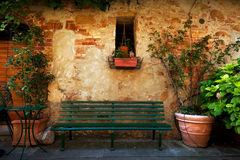 Retro bench outside old Italian house in a small town of Pienza, Italy. Vintage Royalty Free Stock Photography