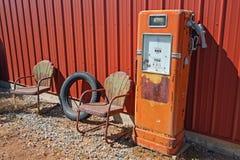 Retro benzinepomp en geroeste stoelen Stock Afbeelding