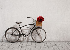 Retro bicycle with basket and flowers in front of the old wall, background. Retro black bicycle with basket and flowers in front of the old plaster wall, red Stock Photos