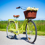 Retro bicycle with wicker basket and flowers in countryside Royalty Free Stock Image