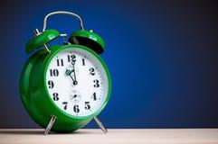 Green alarm clock. Retro big green alarm clock on blue background Stock Photography