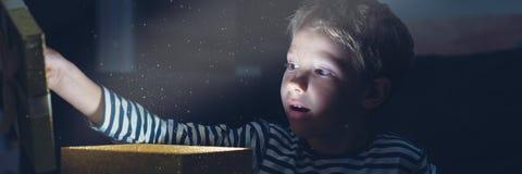 Retro bild för bred sikt av en litet barnpojke med ett förvånat uttryck på hans framsida, som han öppnar en guld- gåvaask med lju arkivbild
