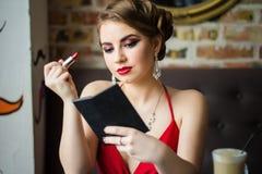 retro bild Flickan målar hennes röda läppstift för kanter royaltyfria foton