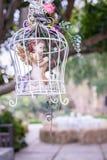 Retro- Birdcage mit schönen Blumen im Garten Stockbilder