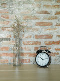 Retro black alarm clock and bottle glass of dry flower on wooden table. Royalty Free Stock Photography