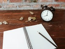 Retro black alarm clock, dry leaves, blank notebook and pencil on wooden table Royalty Free Stock Photography