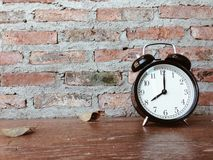 Retro black alarm clock and dry leaves on wooden table Stock Photography