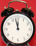 Retro Black Alarm Clock with Red Background. Almost noon or midnight on a Retro Black Alarm Clock with Red Background Royalty Free Stock Images