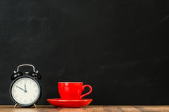 Retro black alarm clock with red coffee cup set. On wood texture floor in blackboard wall background art studio show inspiration ideas creative area Royalty Free Stock Photography
