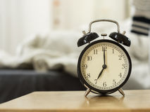 Retro black alarm clock show 7 o'clock in the morning for wake u. P.Background is a bedroom Stock Images