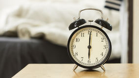 Retro black alarm clock show 6 o'clock in the morning. For wake up.Background is a bedroom Stock Image