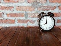 Retro black alarm clock on wooden table Royalty Free Stock Photography