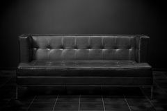 Retro black sofa in dark room Stock Images