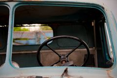 Retro black steering wheel inside old and abandoned blue truck. Oldtimer steering wheel Stock Images