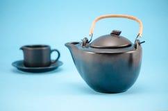 Retro black tea pot cup saucer composition blue Stock Photo
