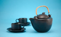 Retro black teapot cups saucers composition blue Stock Photography