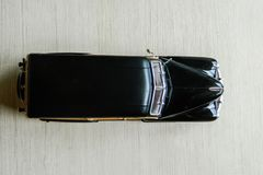 Retro black toy car on gray striped surface. Model of classic vintage sport car with shadows and partly soft focus. Top view of. Auto with yellow brown doors royalty free stock images