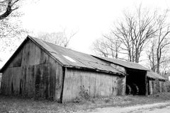 Old Farm Tractor Shed. A retro black and white fall image of a rustic old wooden farm barn used to shelter tractors and other equipment on a small farm in the Royalty Free Stock Photos