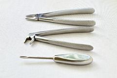 Retro. Black and white photography. Metal dental instruments for removing teeth on sterile white gauze background stock photo