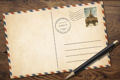 Retro blank postcard with pen on old wood table stock illustration