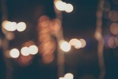 Retro blauwe gestemde vage achtergrond van chrismaslichten met straatlantaarns op de nachtstraat in uitstekende stijl Stock Fotografie