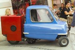 Retro blauwe miniauto met rode aanhangwagen die zich in stad bevinden Stock Foto