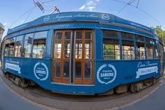 Retro blauwe tram met passagiers op de straat in Milaan, Italië Stock Foto