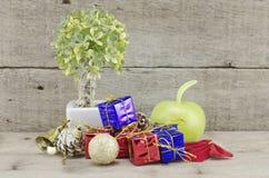 Retro- Blick Weihnachtsdekorationen mit rotem Ball, grünem Ball, rotem Band, Glocke, samll Baum auf weißem Topf und künstlicher B Lizenzfreies Stockbild