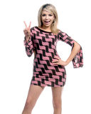 Retro Blond Peace Sign. Beautiful young blond in a pink and brown retro dress giving the peace sign Stock Photo