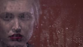 Retro blonde woman with red earrings is sad, rain drops on the window, close up. Sad blonde woman with red lipstick and earrings is looking through the window stock video footage