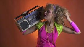 Retro blondevrouw in de jaren '80uitrusting met boombox op haar shouldre die aan de muziek dansen en met haar haar spelen stock footage