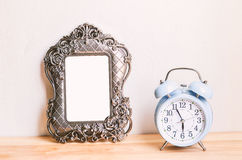 Retro blue alarm clock with traditional picture frame on wooden Stock Images