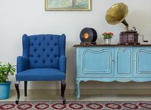 Retro blue armchair and vintage wooden light blue sideboard. Vintage interior of retro blue armchair, vintage wooden light blue sideboard, old phonograph royalty free stock images