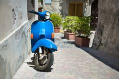 Retro blue scooter. In old town narrow street Royalty Free Stock Photography