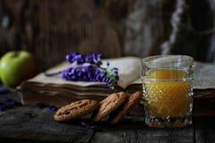 Retro bok och exponeringsglas av orange fruktsaft i morgon Fotografering för Bildbyråer