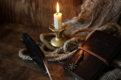 Retro book candle and feather Royalty Free Stock Image