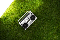 Retro boom box receiver over fresh green grass Royalty Free Stock Photography