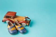 Retro bottini del cuoio del bambino con l'automobile d'annata del giocattolo Immagine Stock