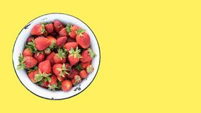 Retro bowl of fresh strawberries from own field, isolated on a yellow background, top view, copy space for text stock images