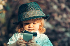Retro boy with phone in blossom Royalty Free Stock Photography
