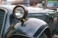 Retro bronsbil för pannlampa i regnväder Arkivbild