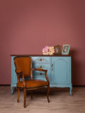 Retro brown leather armchair near blue dresser. Tender bouquet and two frames. Blue and brown vintage interior. Brown room with ethnic dresser and chair stock photos