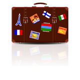 Retro brown leather suitcase with stickers from his travels. Royalty Free Stock Images