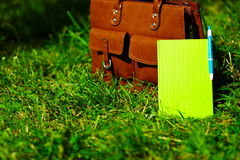 Retro brown  man leather bag and notebook in bright colorful summer grass Stock Image