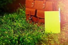 Retro brown  man leather bag and notebook in bright colorful summer grass Royalty Free Stock Photography