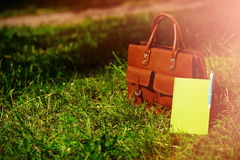 Retro brown  man leather bag and notebook in bright colorful summer grass Royalty Free Stock Photos
